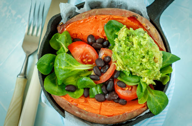 Baked whole sweet potato with guacamole and black beans in a cast-iron frying pan. Love for a healthy vegan food concept