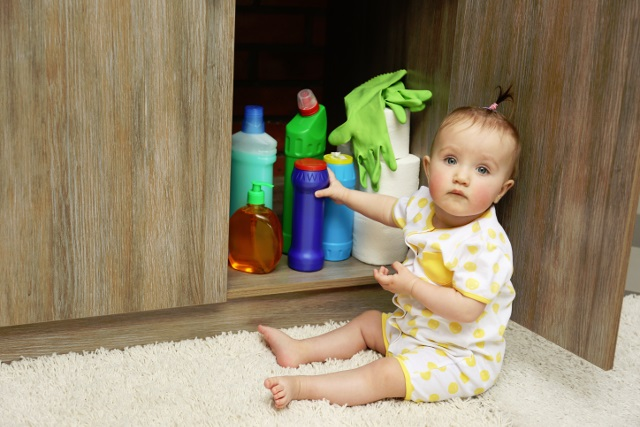 Child playing with kitchen chemical and detergents
