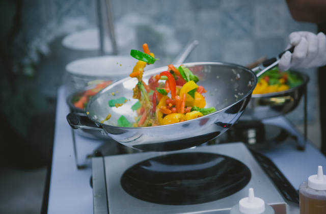 Cooking vegetables in a wok pan