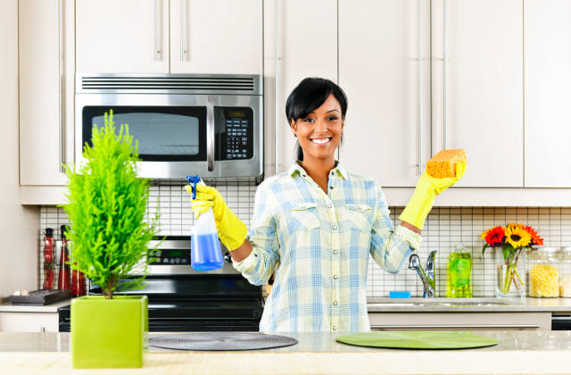 Happy young woman cleaning the kitchen