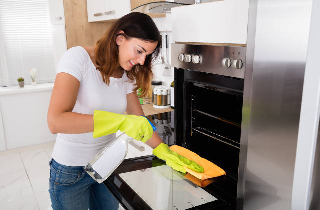 Woman cleaning the oven