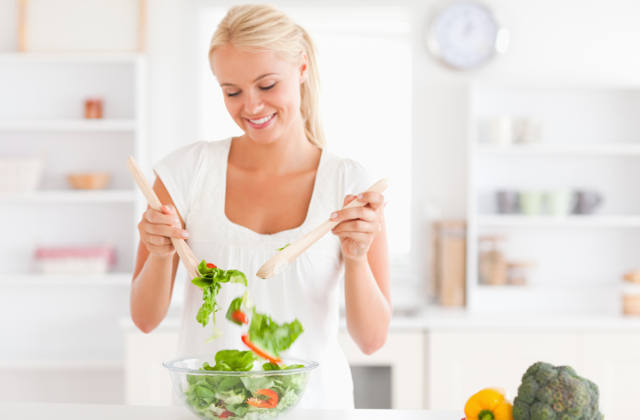 Woman mixing a salad in her kitchen