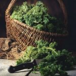 fresh Kale in a Basket on a wooden Table